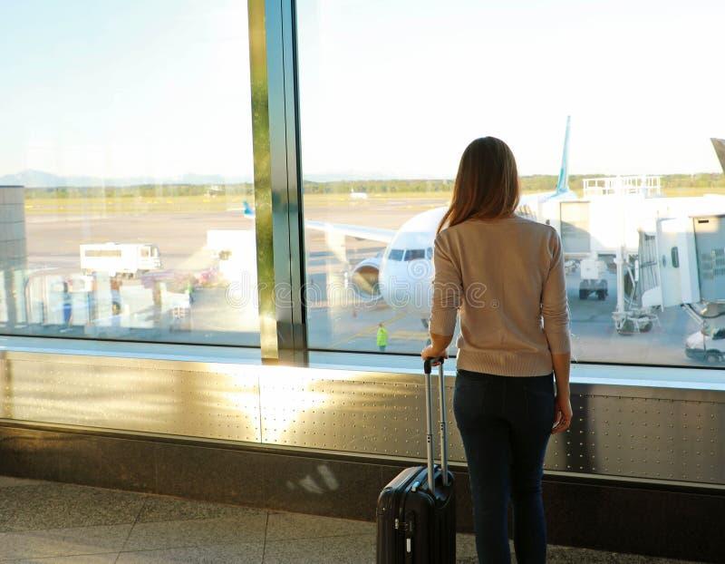 Задняя молодая женщина взгляда с чемоданом в современном крупном аэропорте стоковая фотография rf