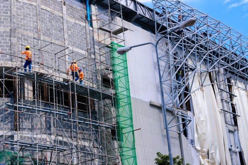 Задняя сторона рабочий-строителей работает na górze структуры здания с ярким голубым небом и белой предпосылкой облака стоковая фотография rf