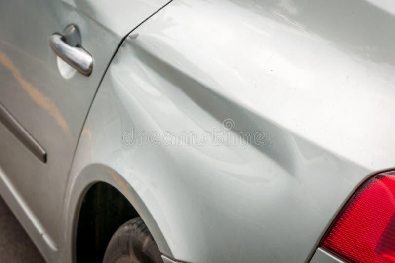 Задняя сторона сломленной и поврежденной серебряной автомобильной катастрофы в аварии аварии с поцарапанной краской в конце столк стоковое фото