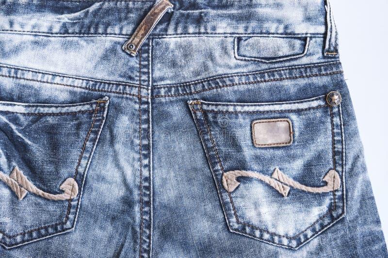 Задняя сторона текстуры с карманн, конца-вверх голубых джинсов джинсовой ткани стоковая фотография