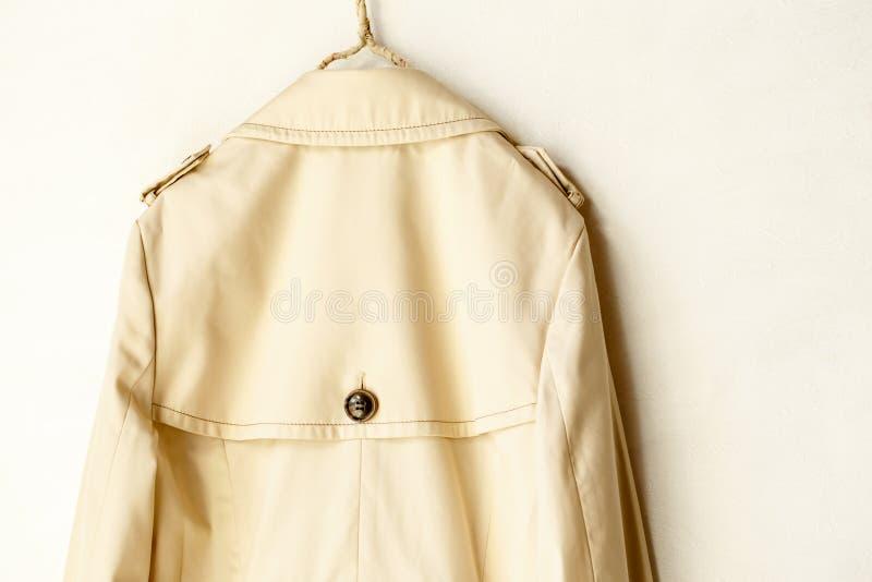Задняя часть бежевого элегантного пальто канавы изолированного над белизной стоковое фото