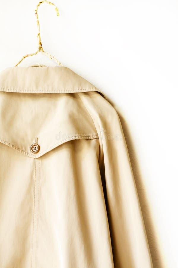 Задняя часть бежевого элегантного пальто канавы над белизной стоковое изображение rf