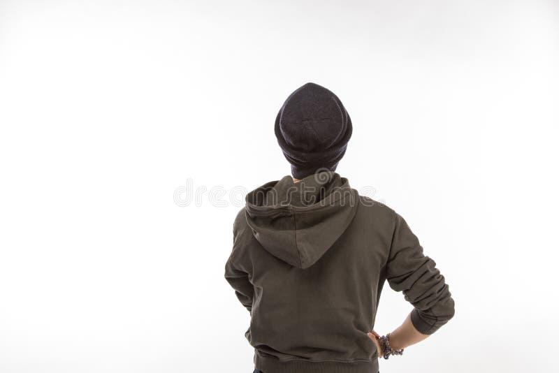 Задняя часть подростка в темных hoodie и шляпе фуфайки на белой предпосылке изолированной на белой предпосылке стоковая фотография rf
