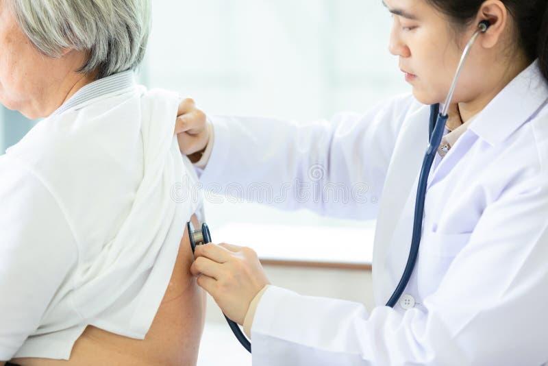 Задняя часть слушая пациента женского врача через стетоскоп, азиатский доктора или медсестру проверяя сердце и легких старших люд стоковое фото rf