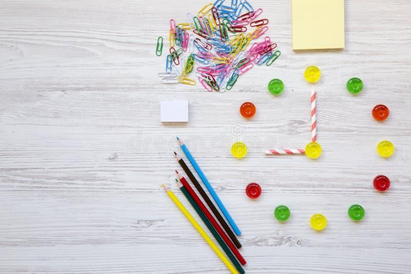 задняя школа к Часы сделанные из красочных сладостных конфет Часы ` 9 o на вахте Аксессуары для исследования на белой деревянной  стоковые фотографии rf