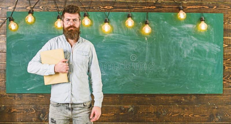 задняя школа принципиальной схемы к Бородатый битник держит книгу, доску на предпосылке Человек с бородой и усик на серьезном стоковое фото