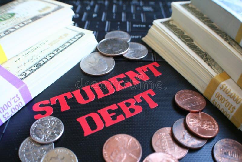 Задолженность студента с стогами денег на клавиатуре компьтер-книжки высококачественной стоковые изображения