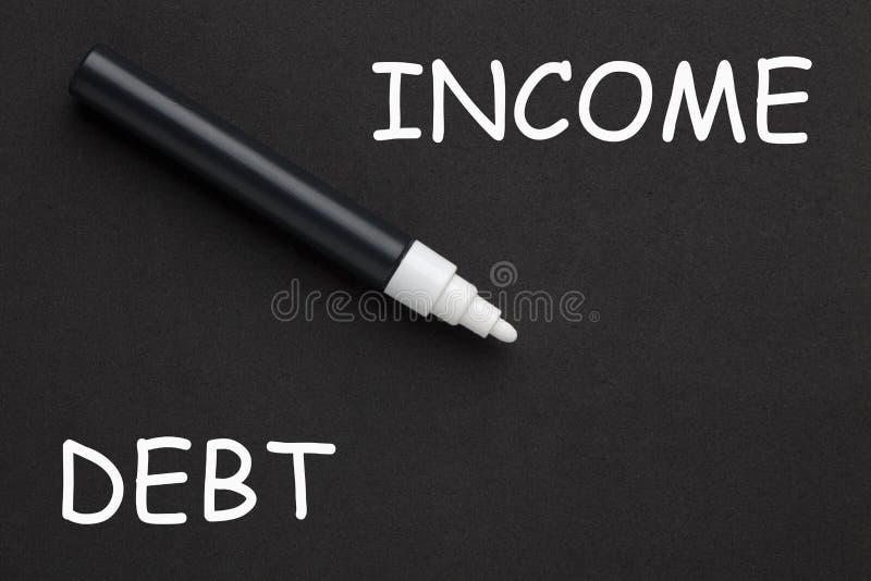 Задолженност-к-доход написанный на черной предпосылке стоковые фото