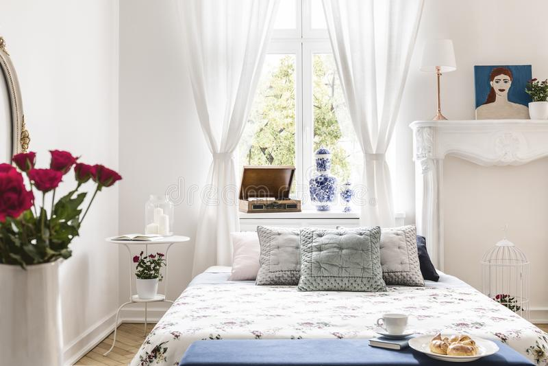 Задрапировывает на окне над кроватью с валиками в белом interi спальни стоковое фото