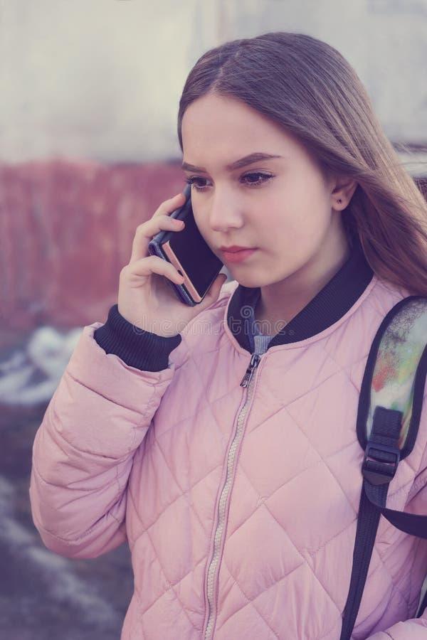 Задумчивая девушка говоря на телефоне стоковое изображение