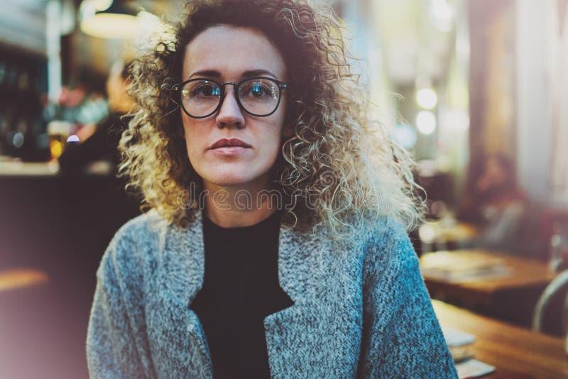 Задумчивая женщина в стеклах глаза стильной одежды нося снаружи в европейском городе ночи Bokeh и влияние пирофакелов дальше стоковые фотографии rf