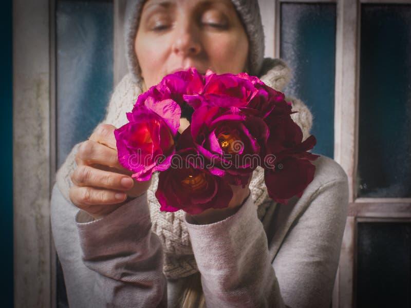 Задумчивая женщина держит красивые фиолетовые цветки в ее ha стоковое фото rf