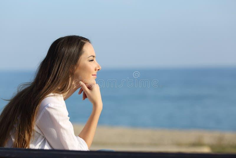 Задумчивая женщина смотря вперед на пляже стоковая фотография
