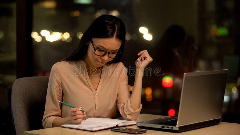 Задумчивая коммерсантка думая о тетради сочинительства плана, сидя фронта ноутбука стоковая фотография rf