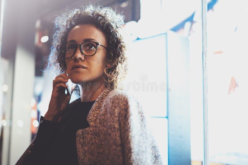 Задумчивая милая женщина звоня переговора с ее друзьями через телефон клетки пока стоящ на ноче на улице стоковое фото rf