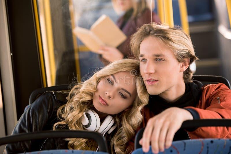 задумчивые красивые молодые пары смотря прочь пока сидящ совместно стоковое фото