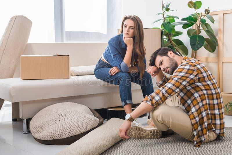 задумчивые молодые пары на новом доме с двигать картонных коробок стоковая фотография rf