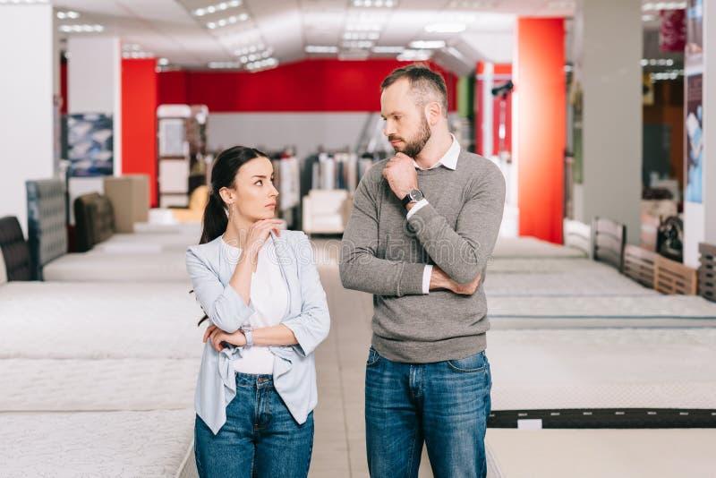задумчивые пары смотря один другого в мебельном магазине стоковое фото rf