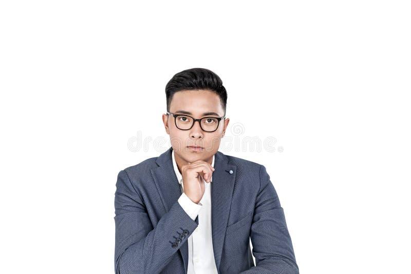 Задумчивый азиатский бизнесмен в изолированных стеклах, стоковые изображения rf