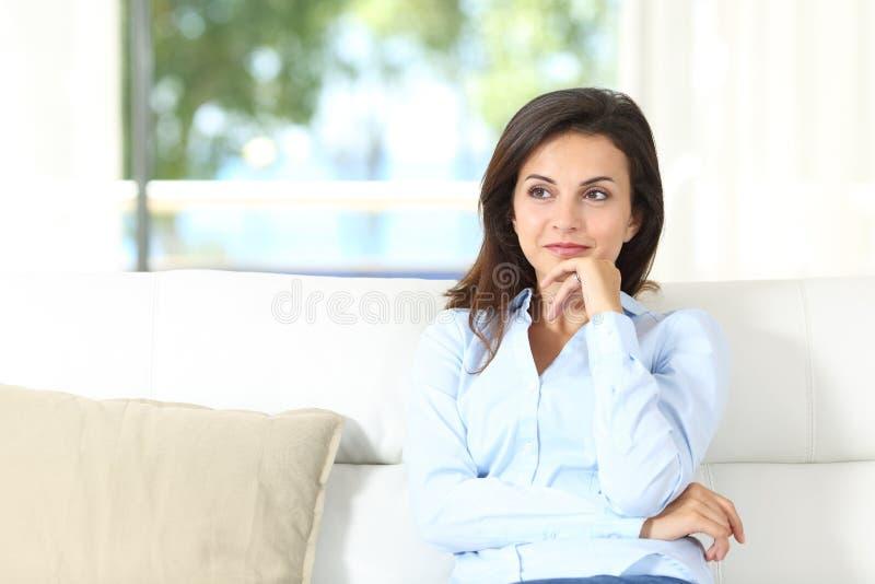Задумчивый домовладелец сидя на кресле дома стоковая фотография rf
