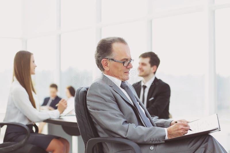 Задумчивый зрелый бизнесмен в костюме с его командой работая позади стоковое фото rf