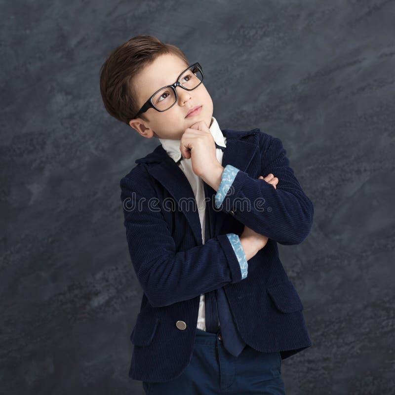 Задумчивый мальчик внутри в черном костюме стоковое фото