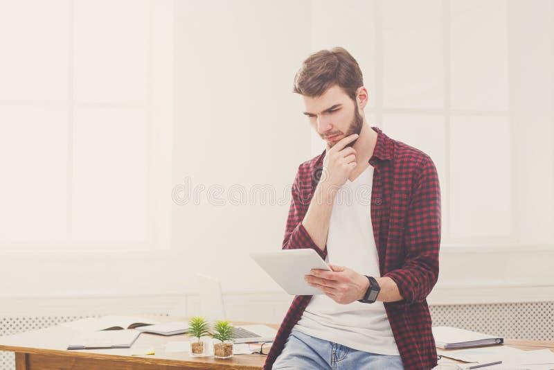 Задумчивый молодой бизнесмен используя цифровое taplet в офисе стоковые изображения