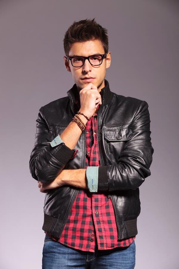 Задумчивый молодой человек с кожаной курткой и стеклами стоковые изображения