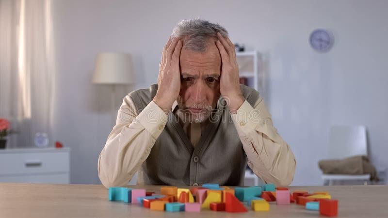 Задумчивый пожилой человек смотря строительные блоки на таблице, слабоумие цвета старости стоковая фотография rf