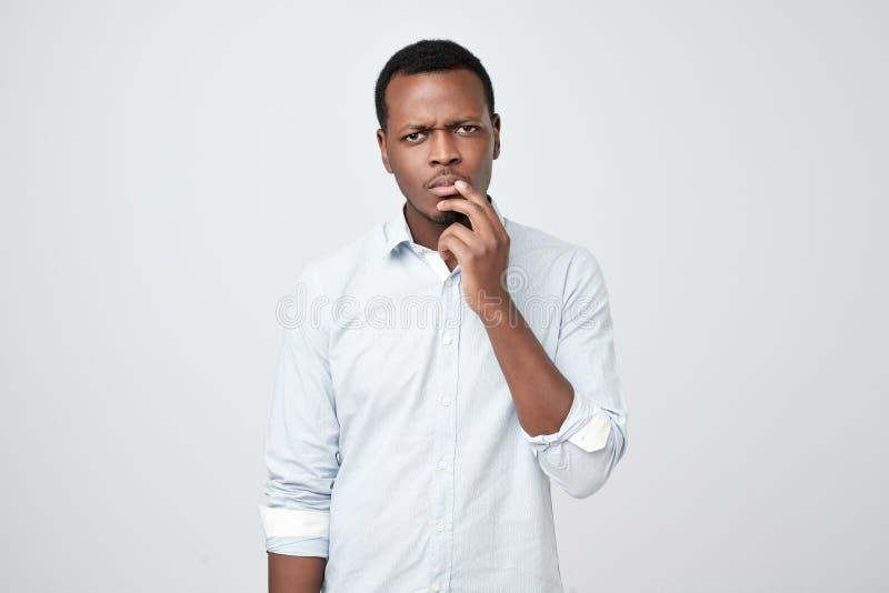Задумчивый серьезный озадаченный африканский человек касаясь его подбородку, выглядящ внимательный и скептичный стоковое фото rf