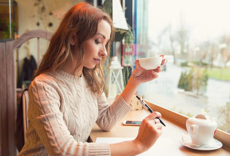 Задумчивый студент изучая и уча принимающ примечания выпивая чай в кофейне стоковые изображения