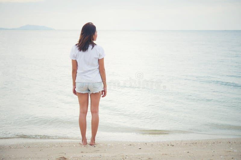 Зад молодой женщины стоя на пляже с barefoot стоковое фото rf