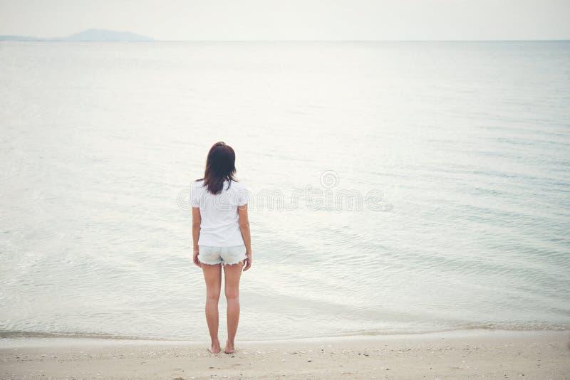 Зад молодой женщины стоя на пляже с barefoot стоковое изображение