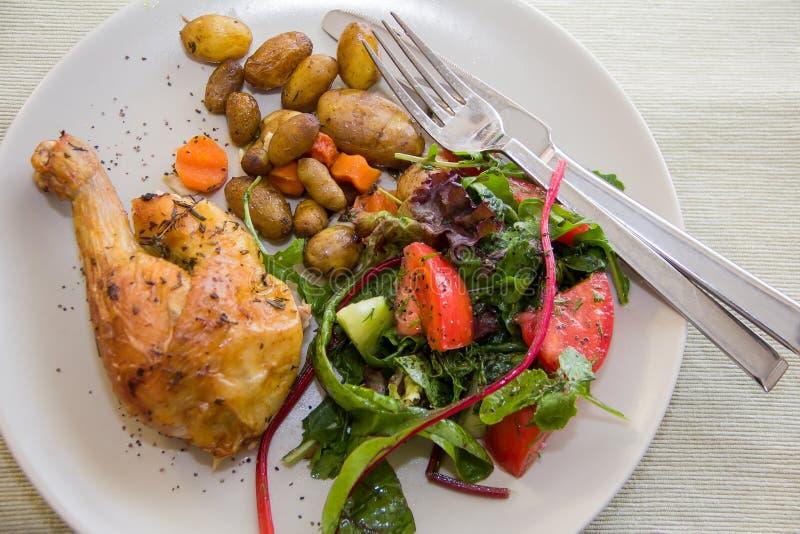 Зажаренная в духовке нога цыпленк цыпленка, картошки и vegetable салат стоковое изображение rf