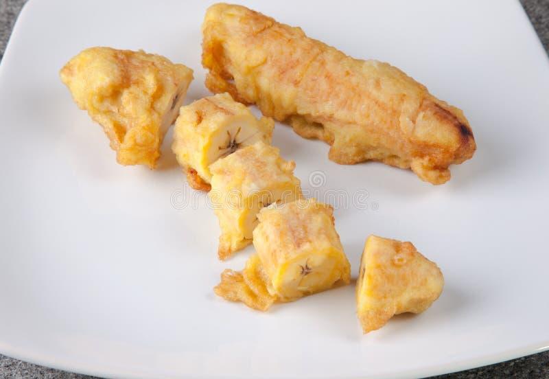 Зажаренная еда Pisang Goreng банана индонезийская отрезанная на белой плите стоковые фотографии rf