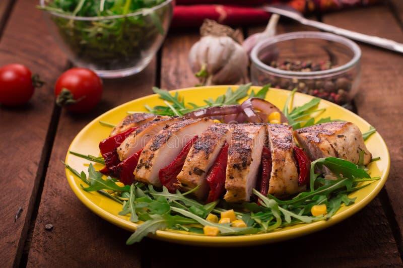 Зажаренная куриная грудка с зеленым салатом от arugula и овощей на желтой плите деревянное предпосылки деревенское Взгляд сверху стоковая фотография