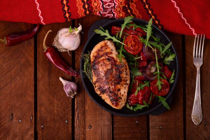 Зажаренная куриная грудка с зеленым салатом от arugula и овощей на черном лотке деревянное предпосылки деревенское Взгляд сверху стоковое фото rf