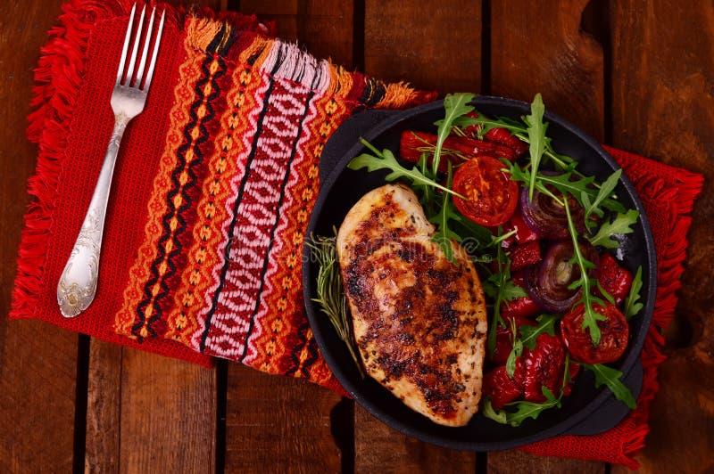 Зажаренная куриная грудка с зеленым салатом от arugula и овощей на черном лотке деревянное предпосылки деревенское Взгляд сверху стоковые изображения