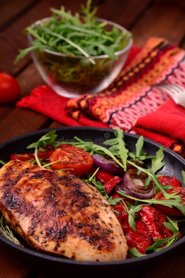 Зажаренная куриная грудка с зеленым салатом от arugula и овощей на черном лотке деревянное предпосылки деревенское Взгляд сверху стоковые изображения rf