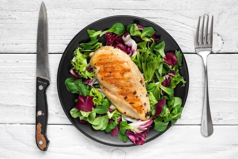 Зажаренная куриная грудка с смешанным салатом на черной плите с ножом и вилкой стоковое изображение rf