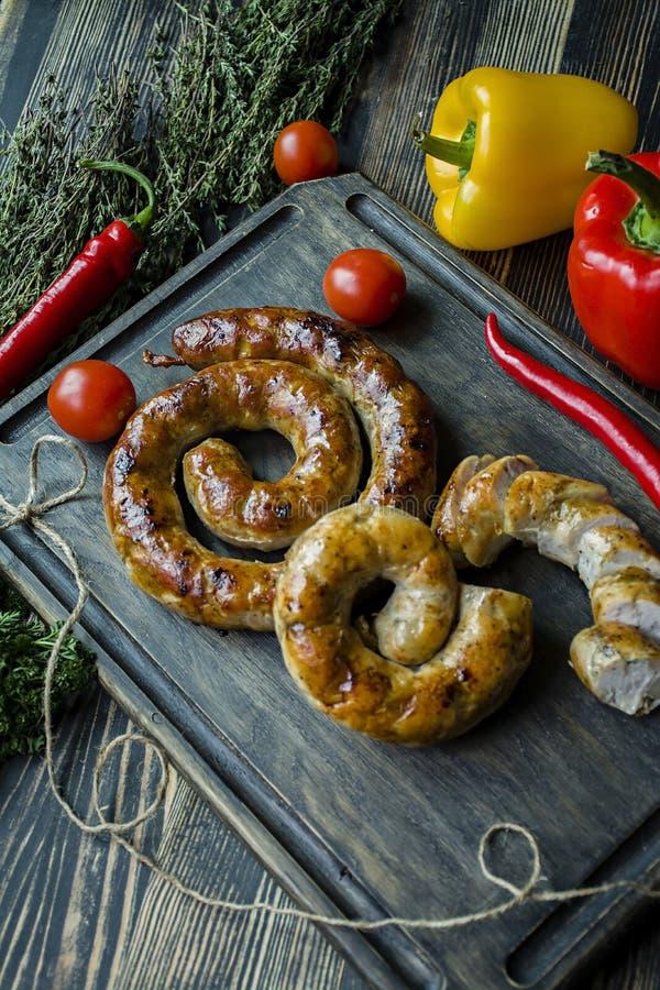 Зажаренная сосиска с травами и специями, деревянной предпосылкой Кольцо испеченной домодельной сосиски Послуженный на деревянной  стоковые фото