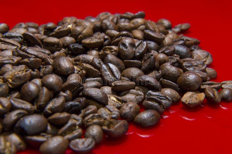 Зажаренное в духовке конца макроса предпосылки кофейных зерен изображение красного поднимающее вверх для cof стоковое фото