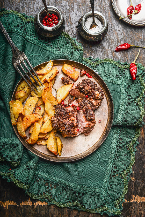 Зажаренное в духовке филе свинины с коркой и испеченной картошкой в плите с вилкой на деревенском кухонном столе стоковые изображения rf