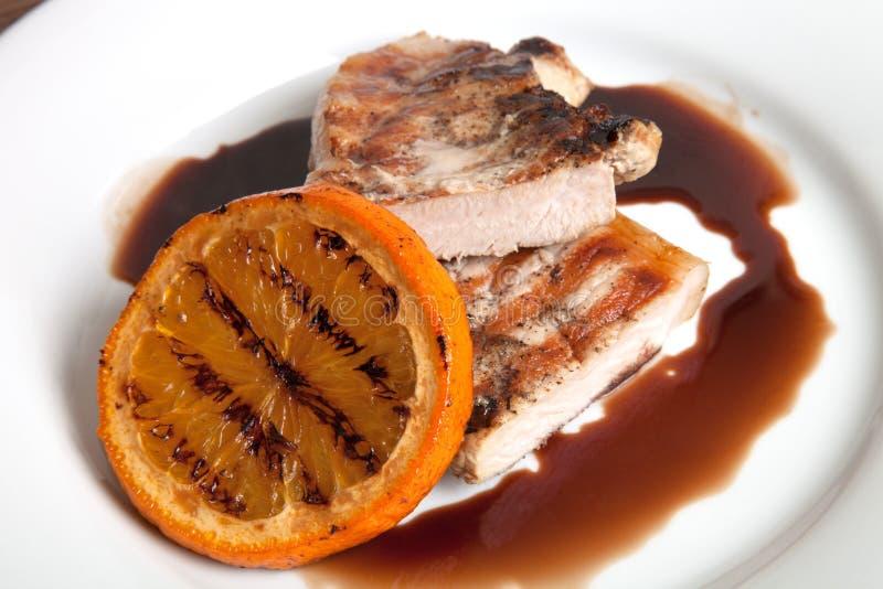 Зажаренное мясо с оранжевым соусом на белой плите стоковое изображение rf