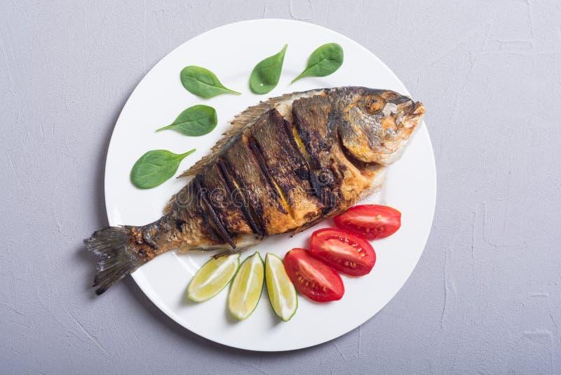 Зажаренное dorado рыб с томатами и шпинатом известки Предпосылка продукта моря стоковые изображения