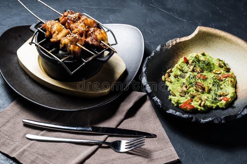 Зажаренное kebab цыпленка с гарниром гуакамоле, темной предпосылкой, взглядом сверху стоковое изображение rf