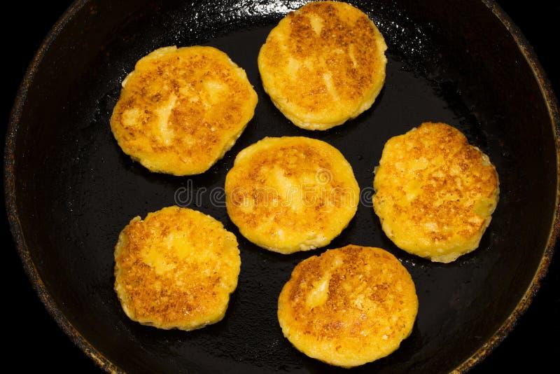 Зажаренные блинчики сыра творога, чизкейки в сковороде, конце вверх стоковые фото