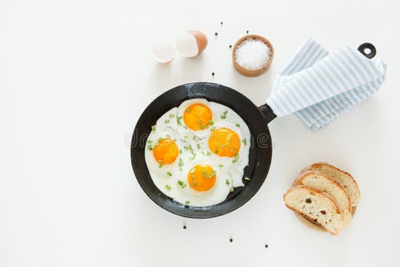 Зажаренные взбитые яйца в сковороде, хлебе и соли на белой предпосылке стоковая фотография rf