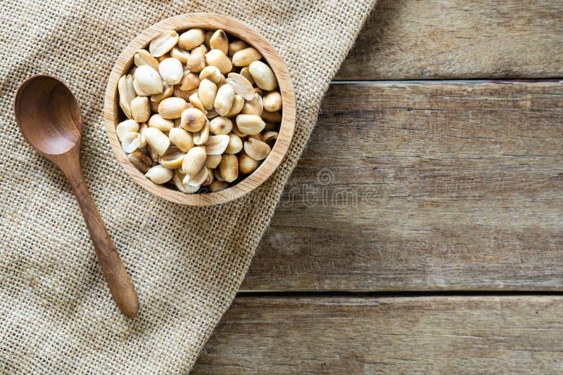 зажаренные в духовке арахисы в деревянном шаре с деревянной ложкой на ткани мешка реднины стоковые фотографии rf