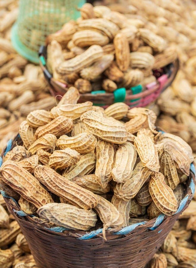 Зажаренные в духовке арахисы в раковине на бамбуковой корзине стоковые фото